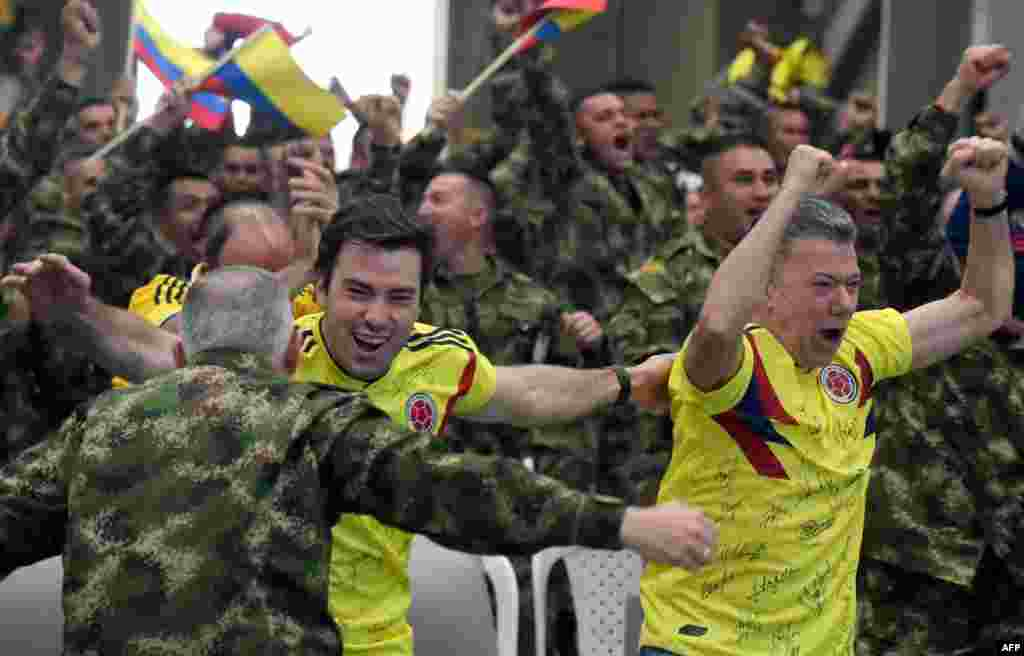 Colombian President Juan Manuel Santos (R) along with his son Esteban (C) and members of the Colombian army celebrate as they follow on a screen the FIFA World Cup match between Colombia and Senegal, at a military base in Tolemaida, Colombia.