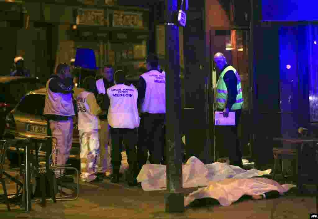 医疗救护人员站在巴黎一家餐馆的受害者身边。(2015年11月13日)