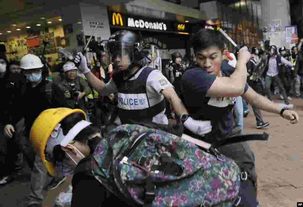 Police officers beat up protesters as they try to disperse them outside government headquarters in Hong Kong. Pro-democracy protesters clashed with police as they tried to surround government headquarters, stepping up their movement for genuine democratic reforms.