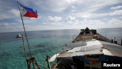 FILE - A Philippine flag flutters a dilapidated Philippine Navy ship that has been aground since 1999 and became a Philippine military detachment on the disputed Second Thomas Shoal, part of the Spratly Islands, in the South China Sea, March 29, 2014.