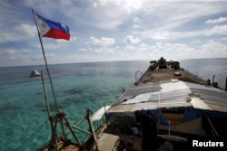 A Philippine flag flutters from BRP Sierra Madre, a dilapidated Philippine Navy ship that has been aground since 1999 and became a Philippine military detachment on the disputed Second Thomas Shoal, part of the Spratly Islands, in the South China Sea, Mar