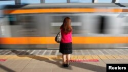 FILE - A woman waits to board a 'women only' passenger train during morning rush hours in Tokyo. The study examined responses from more than 9,600 women employees, submitted by mail or online.