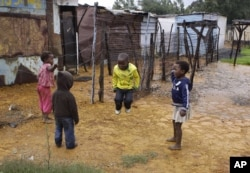 FILE - Children jump rope at the Tudor Shaft squatter settlement near Randfontein, west of Johannesburg, South Africa, Jan. 26, 2011.