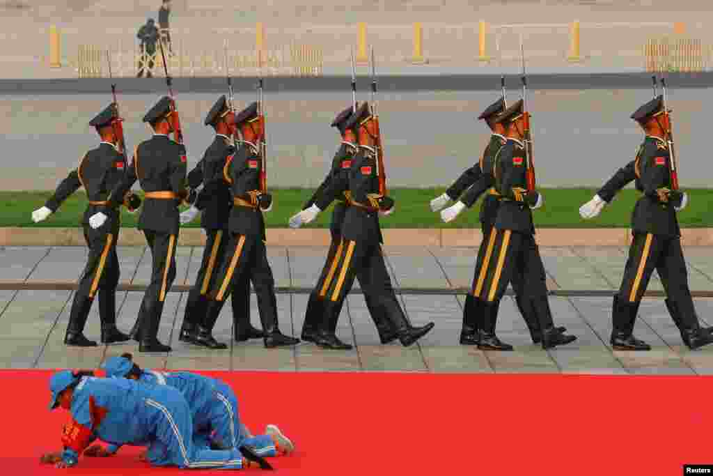 Workers clean a red carpet before a wreath-laying ceremony at the Monument to the People's Heroes in Tiananmen Square, marking the 70th anniversary of the founding of the People's Republic of China, in Beijing, China.