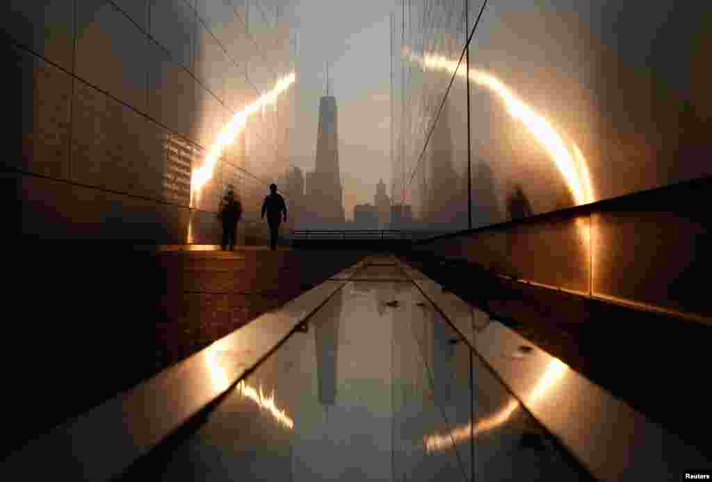 A man walks through the Empty Sky memorial at sunrise across from New York's Lower Manhattan and One World Trade Center in Liberty State Park in Jersey City, New Jersey, Sept. 11, 2013.