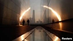 A man walks through the 9/11 Empty Sky memorial at sunrise across from New York's Lower Manhattan and One World Trade Center in Liberty State Park in Jersey City, New Jersey, September 11, 2013.