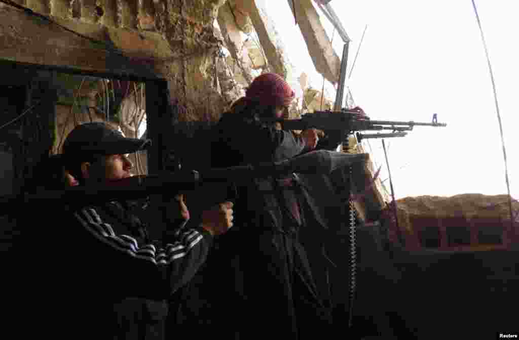 Free Syrian Army fighters with weapons stand guard at the frontline against forces loyal to Syrian President Bashar al-Assad in the Al-khalidiya neighborhood of Homs, December 4, 2012.