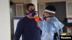 在美国德克萨斯州圣安东尼奥的东南护理康复中心疗养院,身穿防护服的急救人员正在为自己消毒,那里的许多居民和员工都感染了冠状病毒病。(2020年4月4日)