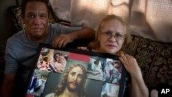 Juan Manuel González y María González Muñoz posan con una foto de Jesús y de su hermana Ramona, una mujer incapacitada de 59 años, quien murió de septicemia en Puerto Rico.
