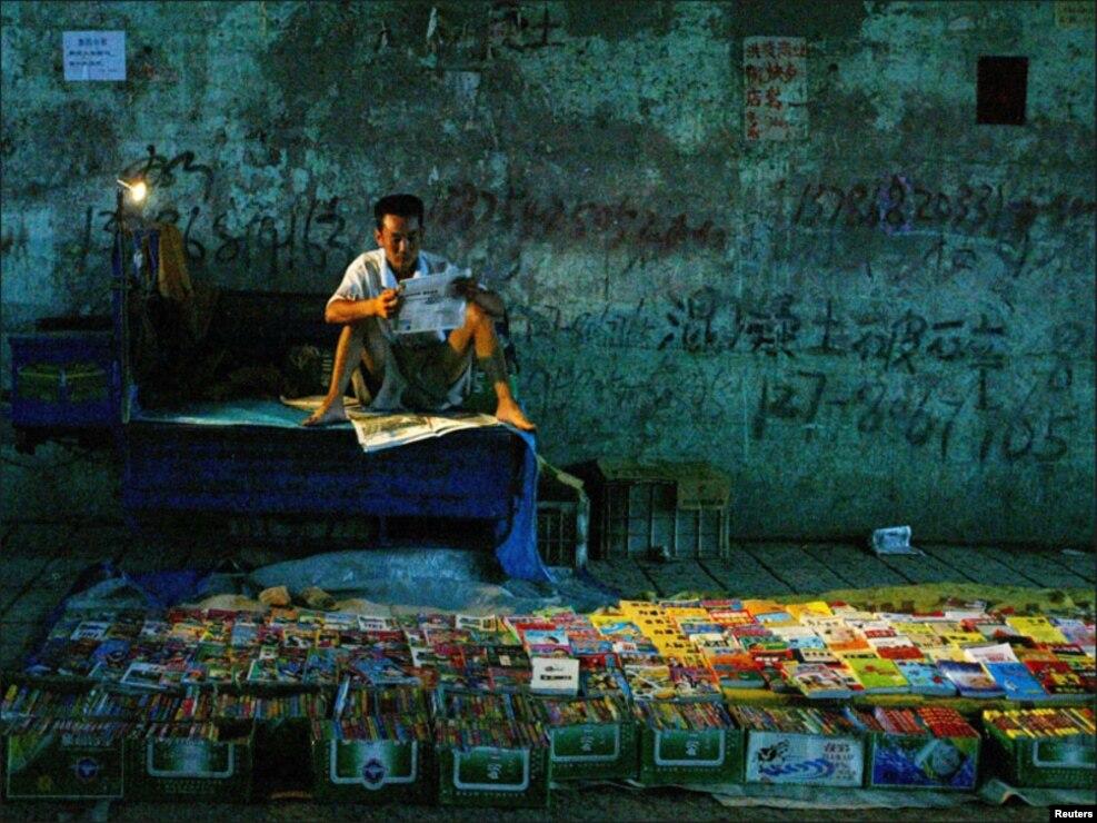 چین کے ایک شہر میں شخص کتابیں فروخت کرنے کے ساتھ ساتھ اخبار کا مطالعہ بھی کررہا ہے