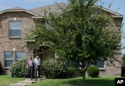 Investigators leave the home of Micah Xavier Johnson in the Dallas suburb of Mesquite, Texas, July 8, 2016.