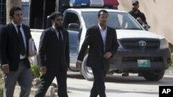 ဘင္လာဒင္၏ အငယ္ဆံုးဇနီး (Amal Al-Sadeh) ယီမင္သူ၏ အကို (Zakarya Ahmad Al-Fattah) (ညာ)၊ ႏွင့္ ေရွ့ေန Amir Khalil (ဘယ္) တို႔ အတူ တရားရံုးသို႔ လာစဥ္