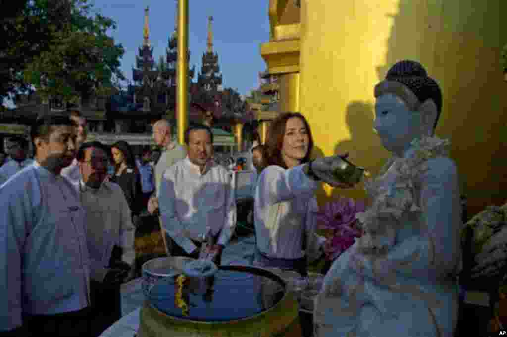 Denmark's Crown Princess Mary pours water on a shrine during a visi to Shwedagon Pagoda, considered as Myanmar's holiest Buddhist shrine in Yangon Saturday, Jan. 11, 2014. Mary, accompanied by Denmark's Minister for Development Cooperation Rasmus Helveg P