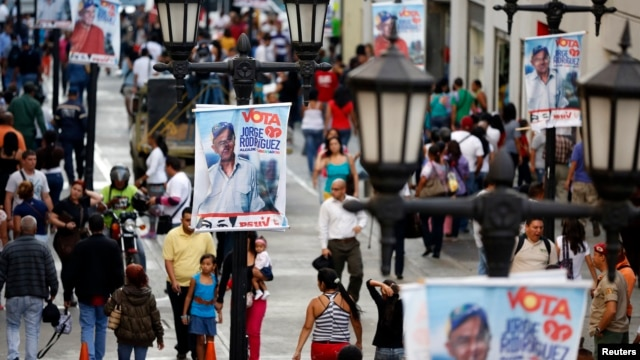 People walk past mayoral election campaign posters of Jorge Rodriguez from the United Socialist Party of Venezuela (PSUV) in Caracas, Dec. 4, 2013.