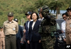 FILE - Taiwan's President Tsai Ing-wen, center, inspects at Su'ao naval station during a navy exercise in the northeastern port of Su'ao in Yilan County, Taiwan, April 13, 2018.