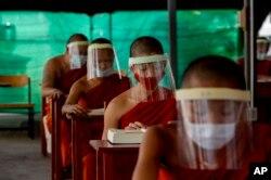 Biksu Buddha muda dengan masker, duduk menjaga jarak sosial berpartisipasi dalam kelas agama di Institut Pendidikan Molilokayaram di Bangkok, Thailand, Rabu, 15 April 2020. (Foto: AP)