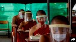بینکاک کے مذہبی سکول میں بچے ماسک اور شیلڈ پہنے پڑھ رہے ہیں۔