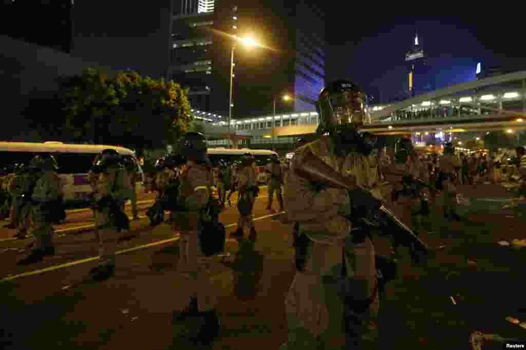 Riot policemen with tear gas launchers stand guard as protesters block the main street to the financial Central district outside the government headquarters in Hong Kong, Sept. 28, 2014.