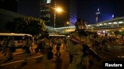 Polisi anti huru-hara dengan gas air mata berjaga-jaga saat para demonstran memblokir jalan utama distrik bisnis pusat kota di luar markas pemerintah di Hong Kong, 28 September 2014.