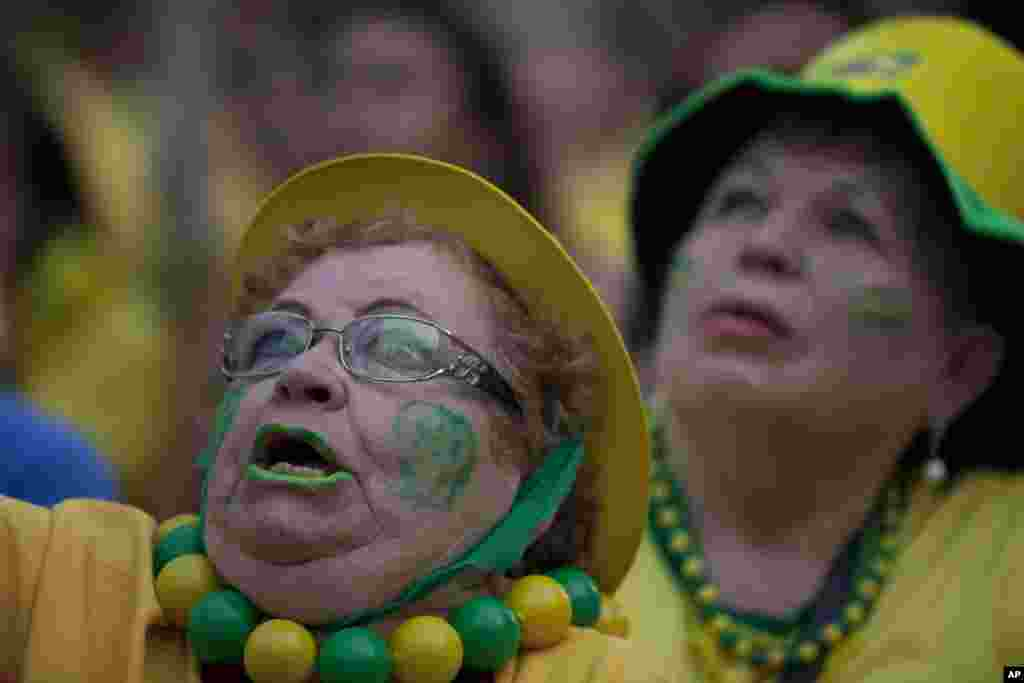 A fan of the Brazilian national soccer team watches the World Cup match against Mexico at the FIFA Fan Fest in Sao Paulo, Brazil, June 17, 2014.