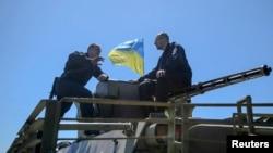 Thủ tướng Ukraina Arseny Yatseniuk (phải) nói chuyện với binh sĩ Ukraine khi ông đến thăm lực lượng Ukraina gần Slaviansk ở miền đông Ukraine, ngày 7/5/2014.