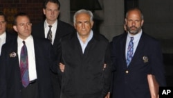 Dominique Strauss-Kahn (C), head of the International Monetary Fund (IMF), departs a New York Police Department precinct in New York late May 15, 2011.