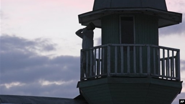Member of Islamic sect calls for evening prayer from atop the house where followers lived in seclusion, Kazan, Russia, Aug. 9, 2012.