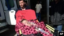 طفل زخمی سوری در حال انتقال به شفاخانه توسط کارمند صحی ترکی
