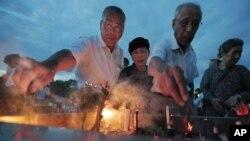 Dân Nhật đốt nhang cầu nguyện tại mộ bia của các nạn nhân của vụ ném bom nguyên tử tại Công viên Tưởng niệm Hòa bình Hiroshima, ngày 6/8/2012