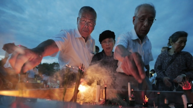 People burn incense and pray in front of the cenotaph dedicated to the victims of the atomic bombing at the Peace Memorial Park in Hiroshima, Japan, August 6, 2012.
