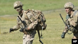 Commander of the 82nd Airborne Division General Richard D. Clarke, left, runs after jumping during a multi-national jump conducted by forces from the U.S., Great Britain and Poland on to a designated drop zone near Torun, Poland, Tuesday, June 7, 2016.