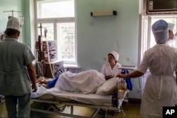 Həkimlər və tibb bacıları Əfqanıstanda hərbi hospitalda yaralanmış insanı müalicə edir
