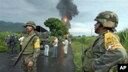Army soldiers stand on a road as a fire rages near the town of Omealca, from a burning facility of the state oil company PEMEX in Maltrata, in the gulf state of Veracruz, Mexico (File Photo - 10 Sep 2010)
