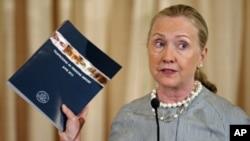 ລັດຖະມົນຕີກະຊວງຕ່າງປະເທດສະຫະລັດ ທ່ານນາງ Hilary Clinton ຍົກປືມລາຍງານ ວ່າດ້ວຍການຄ້າມະນຸດ ປະຈຳປີ 2012 ໃຫເບິ່ງ ທີ່ກະຊວງການຕ່າງປະເທດສະຫະລັດ (19 ມິຖຸນາ 2012)
