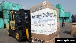 지난 8월 한국 대북지원 민간단체가 북한으로 보내는 장애인.어린이 지원 물품이 인천항에서 컨테이너에 실리고 있다. (자료사진)