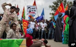 Eritrean refugees and dissidents, some holding Eritrean flags and some dressed as Eritrean military to illustrate beatings and torture, left, demonstrate outside the headquarters of the African Union in Addis Ababa, Ethiopia, June 23, 2016.