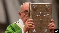FILE - Pope Francis hoists the Gospel book as he celebrates a mass in St. Peter's Basilica at the Vatican, Oct. 5, 2014, to open the extraordinary Synod on the family.