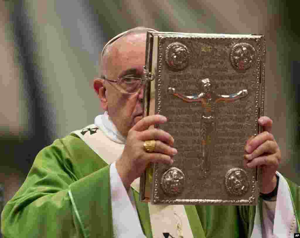 Le pape François hisse l' Evangile lors d'une messe en la basilique Saint-Pierre au Vatican, le 5 octobre 2014, pour ouvrir le Synode extraordinaire sur la famille. (AP Photo / Alessandra Tarantino)