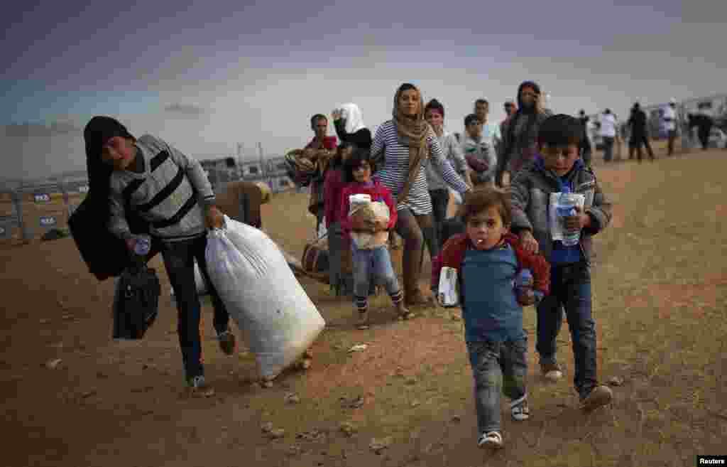 شامی کرد پناہ کے لیے سرحد پار کر کے ترکی میں داخل ہو رہے ہیں۔