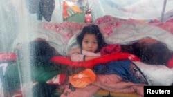 4月22日﹐四川雅安地震災區一名女童在帳篷內向外望﹐帳篷外災區正在下雨。