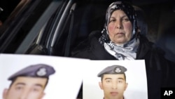 A woman holds a picture of her son, Jordanian pilot Lt. Mu'ath al-Kaseasbeh, who is held by Islamic State group militants, in Amman, Jordan, Jan. 27, 2015.