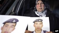 Мать иорданского пилота, лейтенанта Муаза аль-Касасбеха, с портретом сына, взятого в заложники боевиками «Исламского государства». Амман, Иордания. 27 января 2015 г.