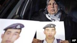 Perempuan Yordania membawa foto putranya, pilot Lt. Mu'ath al-Kaseasbeh, yang masih ditahan oleh kelompok militan ISIS (27/1).