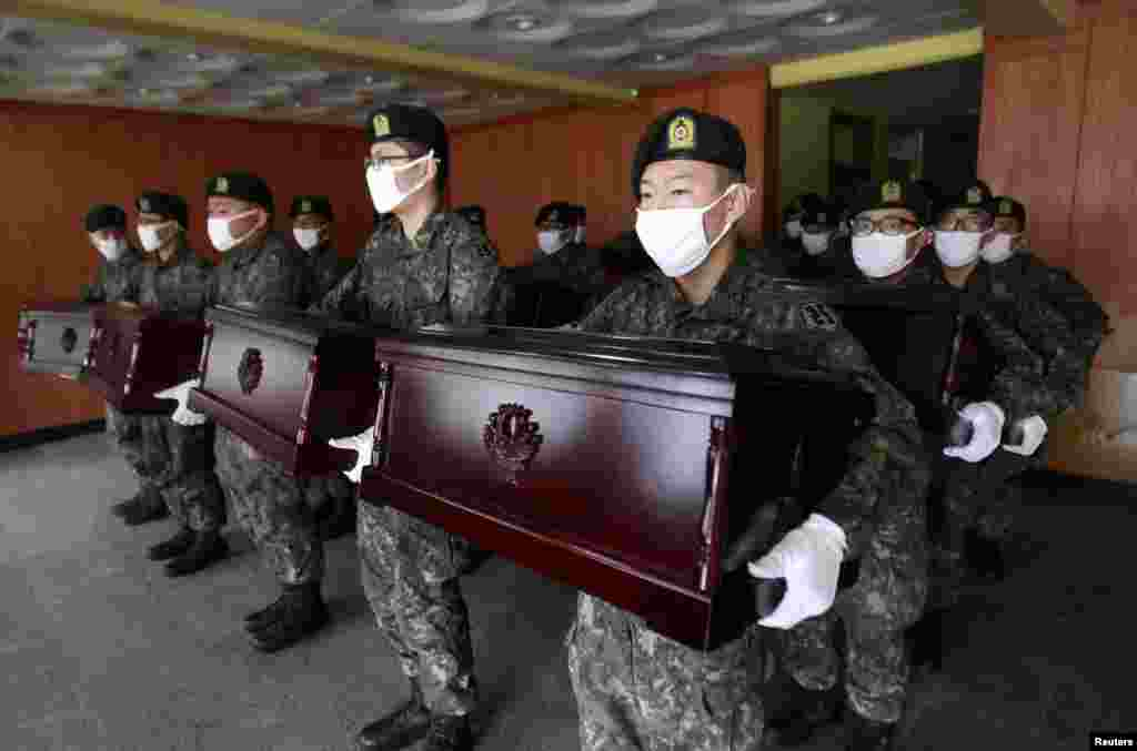 South Korean army soldiers hold caskets containing the remains of Chinese soldiers to be transported to Incheon International Airport, at the temporary columbarium in Paju. The remains of 437 Chinese soldiers killed during the 1950-53 Korean War were transferred from the temporary columbarium in South Korea to the airport to be returned to China.