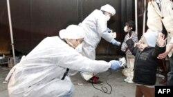 Các viên chức Nhật mặc đồ bảo hộ kiểm tra trẻ em vừa di tản từ khu vực gần nhà máy điện hạt nhân ở Fukushima xem có dấu hiệu phóng xạ hay không