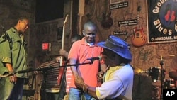 Bluesman Bill 'Howlin Mad' Perry congratulates one of his blues musician students after a set of tunes on stage at the Delta Blues Museum, Nov 2010