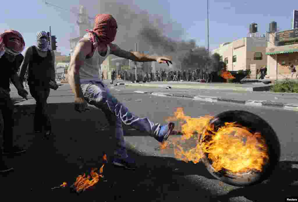 A Palestinian kicks a tire after setting it ablaze during clashes with Israeli police in Shuafat, an Arab suburb of Jerusalem. The discovery of a body in a Jerusalem forest raised suspicions that a missing Palestinian youth had been killed by Israelis avenging the deaths of three abducted Jewish teens.