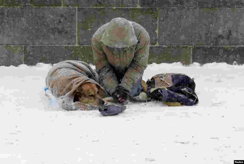 A man with his dog begs for money on the medieval Charles bridge during snowfall in Prague, Czech Republic.