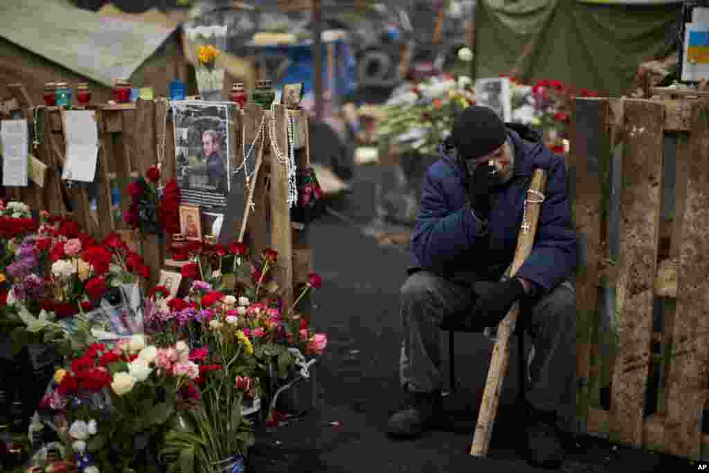 An anti-Yanukovych protester cries near a memorial for the people killed in clashes with police in Ukraine's capital.