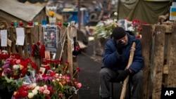 Demonstran anti-Yanukovych menangis dekat peringatan bagi korban tewas dalam bentrokan dengan polisi di Lapangan Kemerdekaan Kyiv.